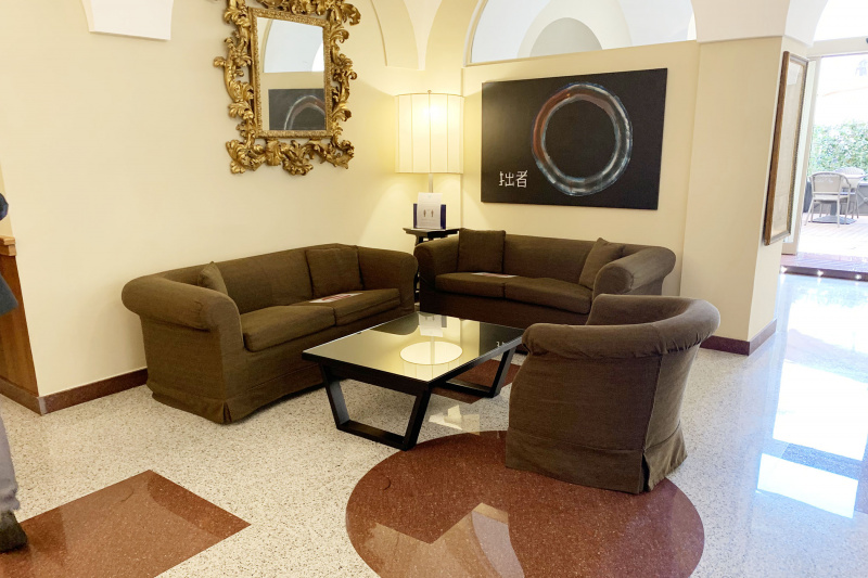The seating area in the lobby includes large couches and granite flooring