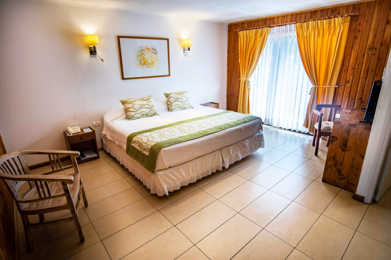 A king-size bed in the middle of a simple tiled room with nightstands on each side and a chair in the corner.