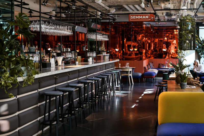 The Bardisk Bar at HOBO hotel has high top chairs, booths, stool seating and smooth floors