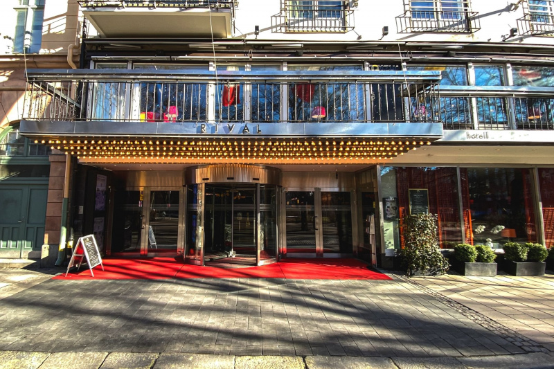 The outside view of Hotel Rival shows carpet flooring, a revolving door, and two french glass doors on each side