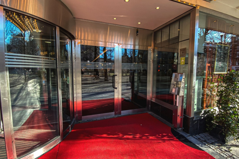 Wide french door entrance to Hotel Rival and red carpet flooring