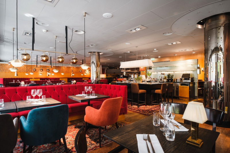 Hotel Rival restaurant has booths, bar tables, and two-person dining tables