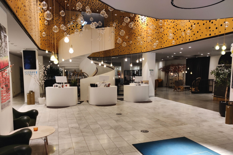 Lobby with upscale seating, chandelier, smooth floors, and circular stairwell.