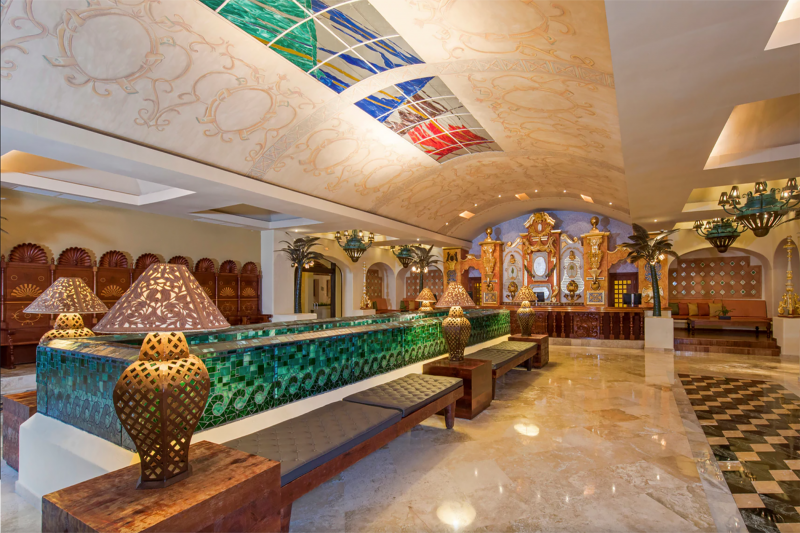 Front desk area with seating and detailed front desk made from wood and mediterranean theme