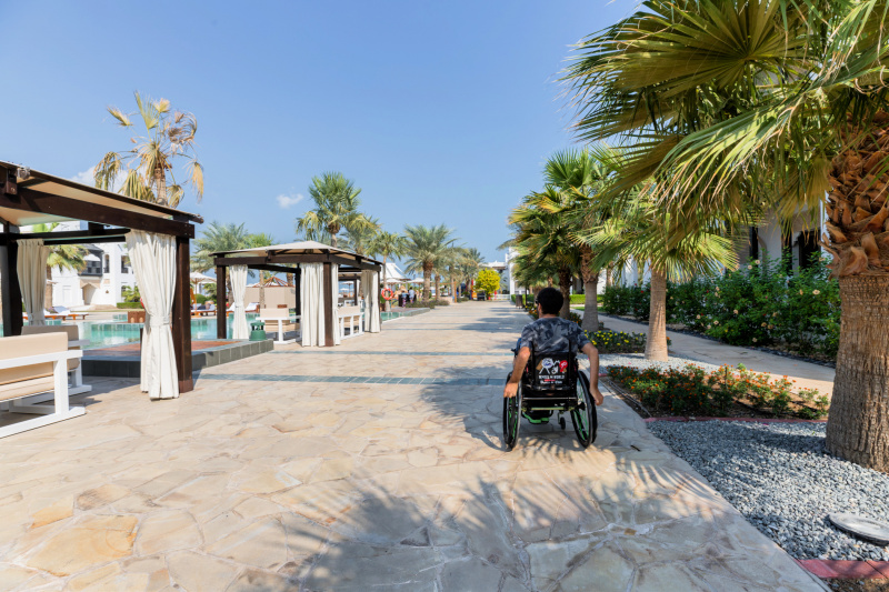 A guest uses a wheelchair to navigate the hotel swimming pool area and cobblestone patio