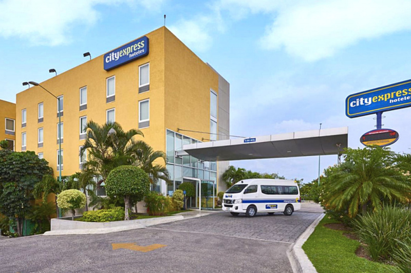 Experior view of City Express Tuxtla Gutiérrez hotel with a drop off area, hotel shuttle, and step free entrance.