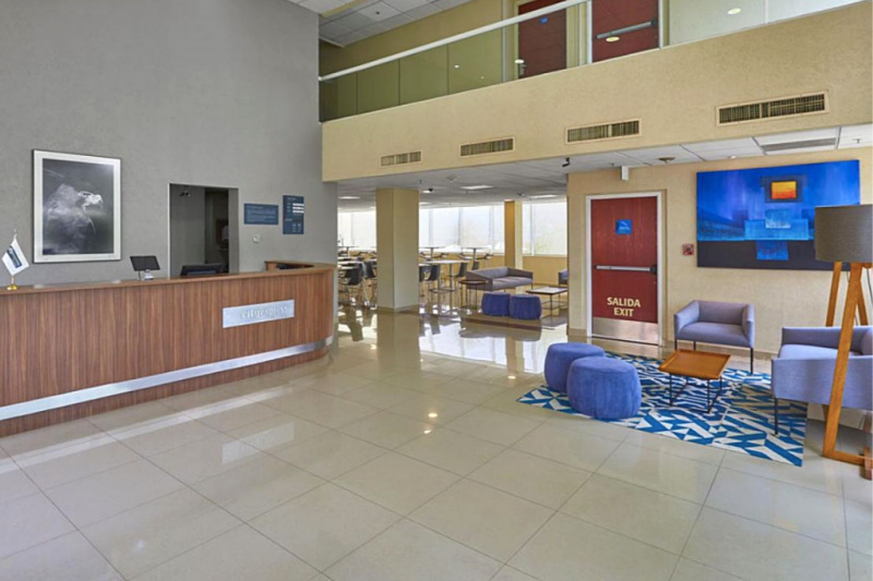Hotel lobby with seating area, standing height front desk, and overhead balcony.