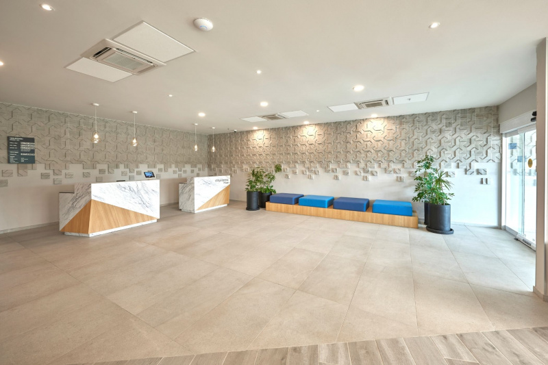 Hotel lobby with minimlaist design hosts two reception desks and bench seating