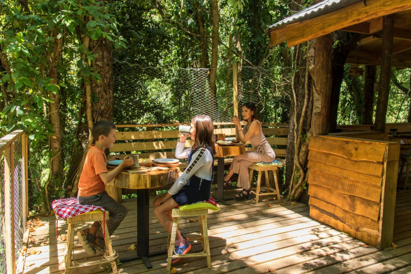 Outside seating with wooden board flooring, tables, and a booth