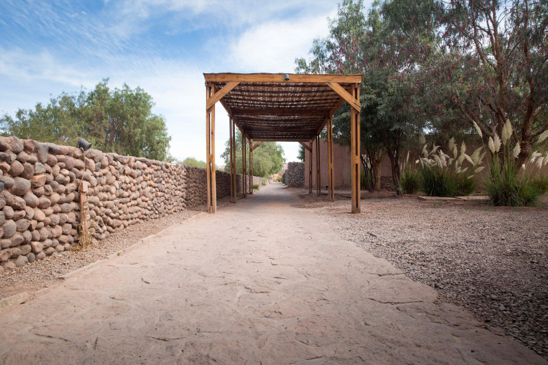 Flat stone pathway with a wooden structure above for shade wooden recycling boxes and cement patio covering ramp.