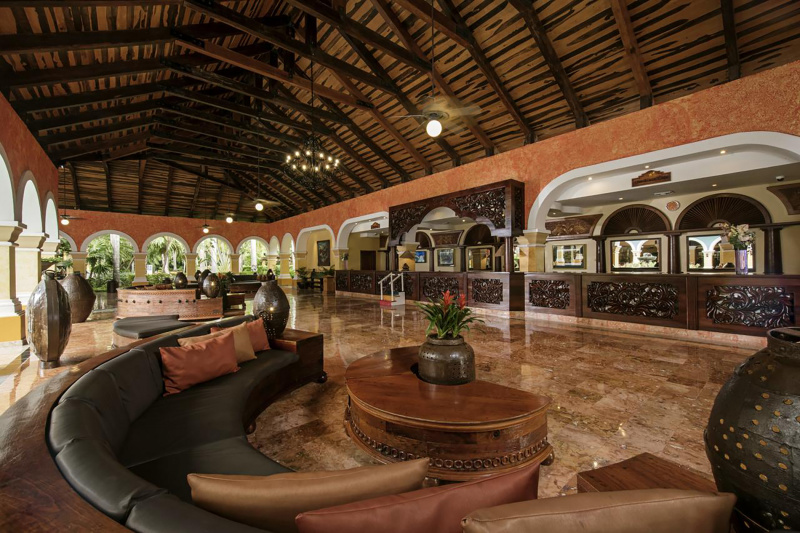 Lobby Iberostar Paraiso Beach with smooth marble floors, vaulted ceilings, and detailed standing height front desk