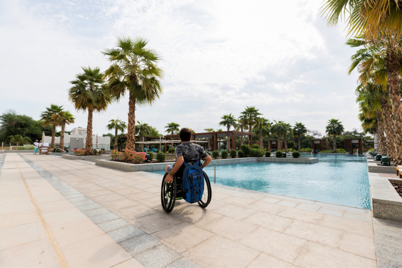 A guest uses a wheelchair to explore the poolside outdooor space