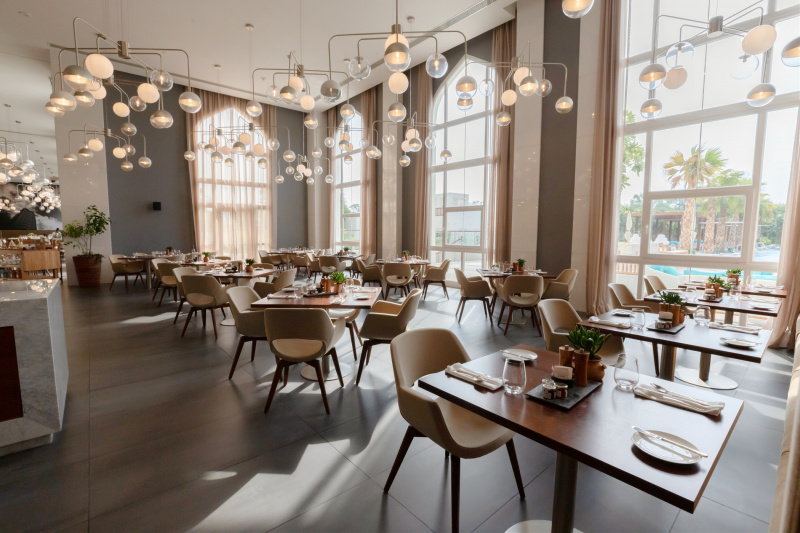Hotel dining space and with tables at an accessible height and floor to ceiling windows
