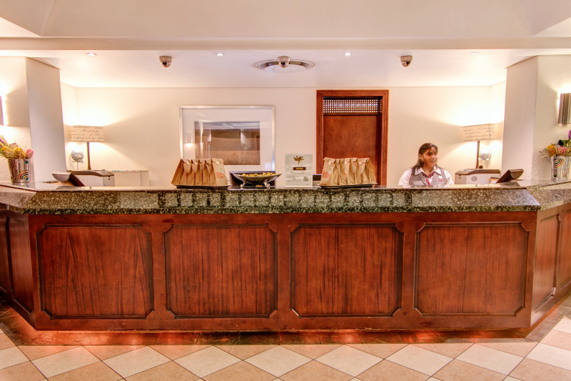 Attendant stands and welcomes guest from behind a raised front desk
