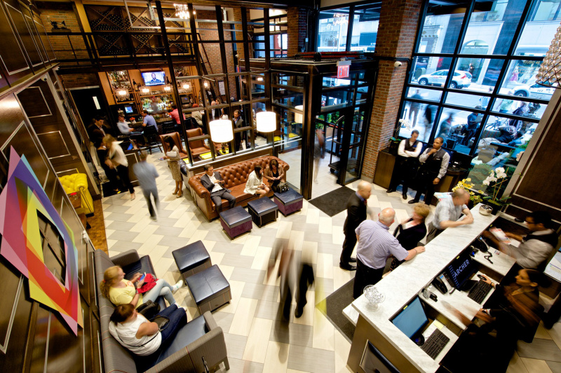 A busy lobby with guests happily moving between the bar and lounge area