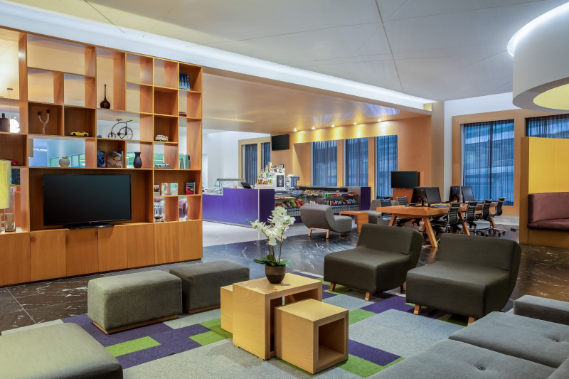Lobby with comfortable seating areas, a television, business lounge area, and a snack bar