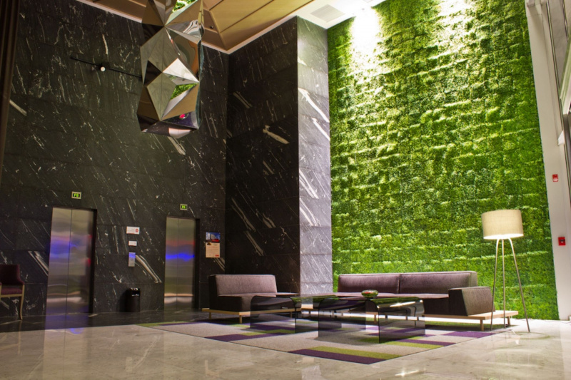 Spacious lobby with two elevators, high ceilings, a plant wall, and a sleek seating area