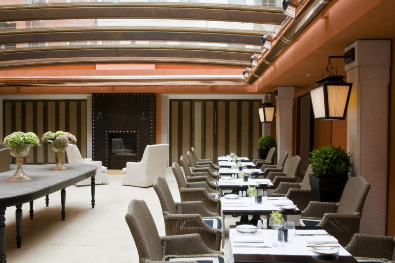 Elegant breakfast area has two seater tables, smooth flooring, and sleek interior design