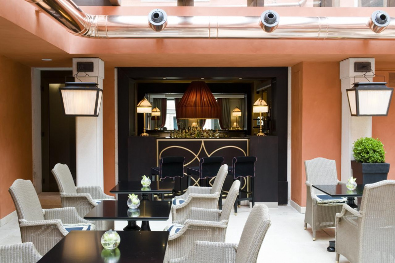 Breakfast area at Splendid Venice has a bar and high top chairs, two seater tables and an elegant interior design