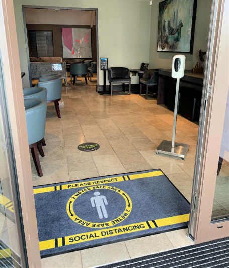 The hotel entrance features a step free doorway, tile floors, wide turn space, a contactless hand sanitizer dispenser, and a welcome mat that informs guests of Covid precautions.