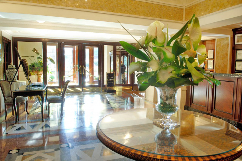 The spacious lobby has a check-in desk, concierge desk, and decorative flower centerpiece