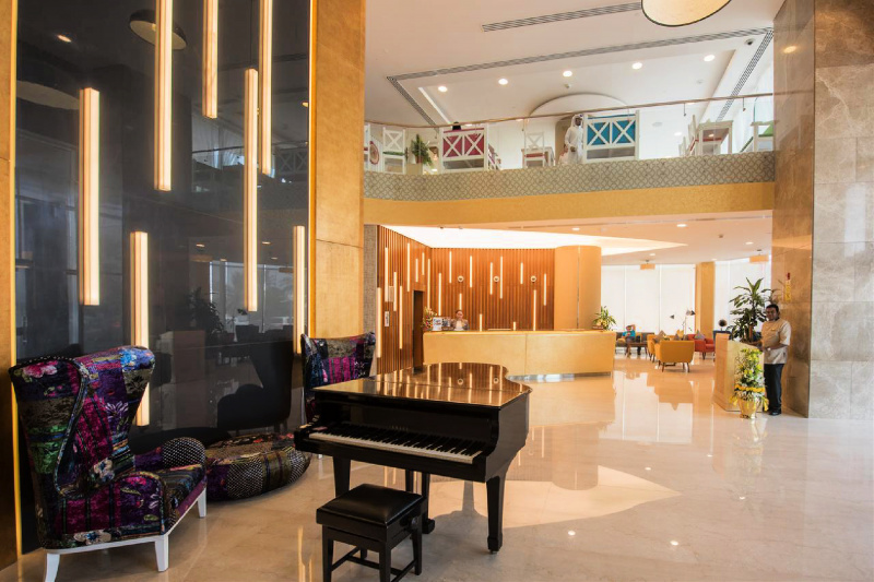 Spacious hotel entrance with a grand piano and smooth floors