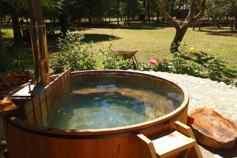 A wooden hot tub heated by fire.