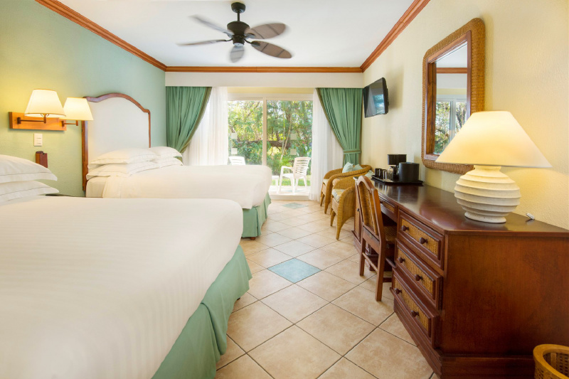Two queen size beds side by side in a tiled room that opens to a private patio.