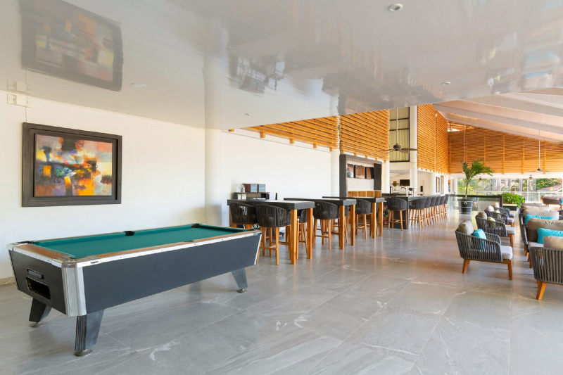 Bar height tables and chairs in an indoor bar with a billiards table.
