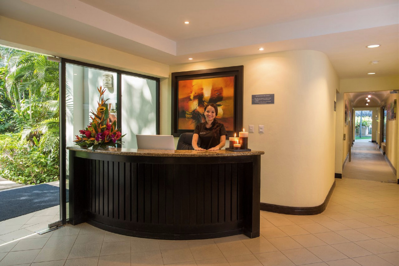 A woman stands behind a wooden front desk.