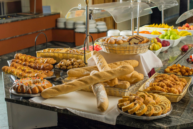 An assortment of pastries, bread, and fruit at a buffet.