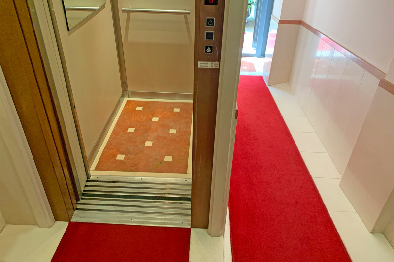 Step free ramped pathway leads to elevator with grab bars