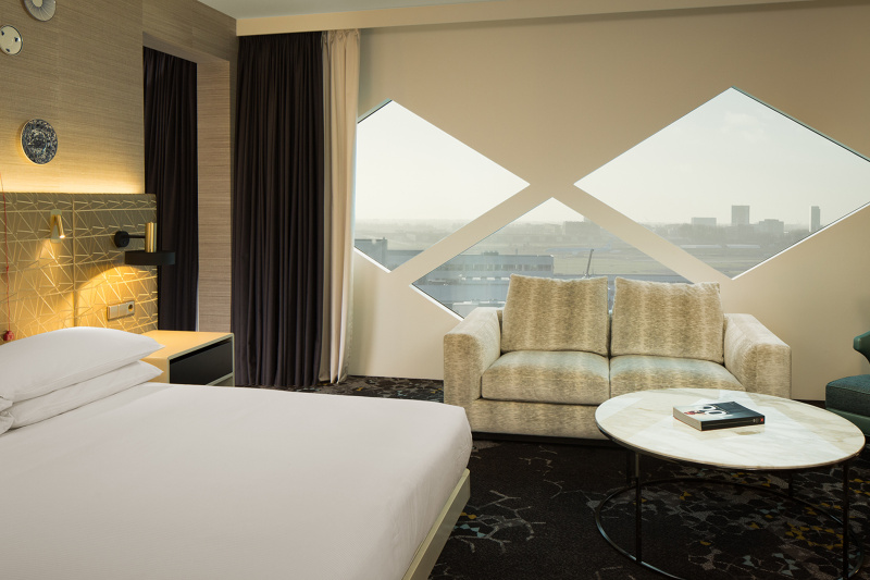 The accessible room has carpet flooring, a two-seater sofa, a coffee table, queen bed, and bedside light controls
