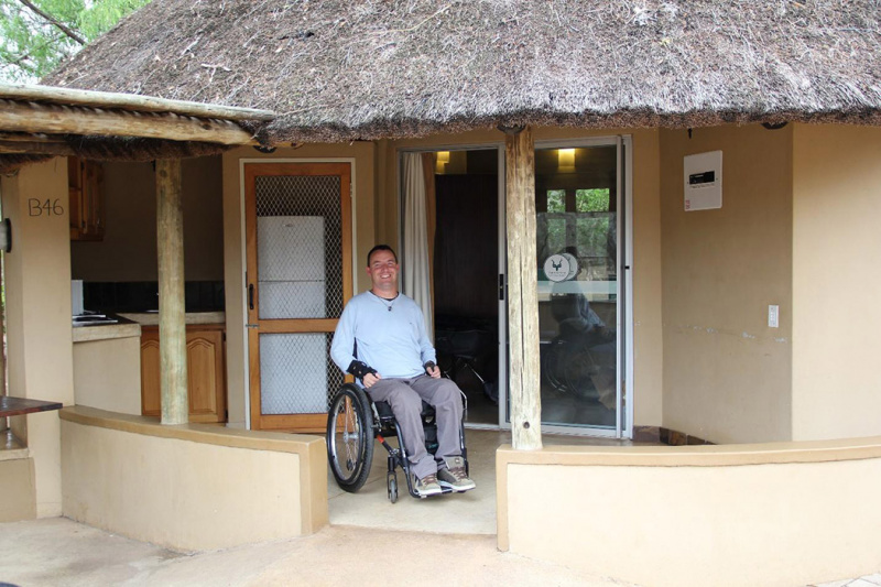 A guest relaxes in their wheelchair in the bungalow's front patio.