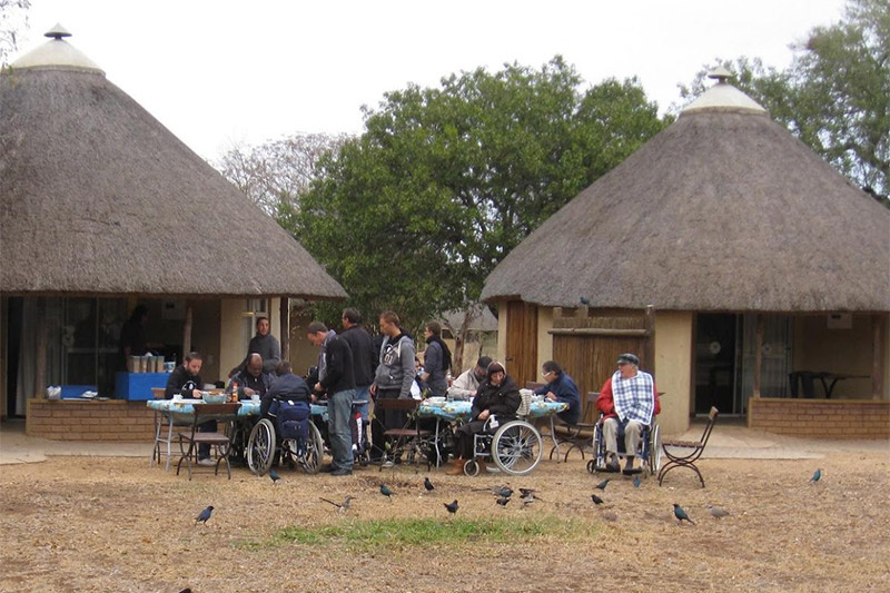 Guest sit outside of the bungalows and enjoy a communal meal nearby paved pathways and a table at an accessible height
