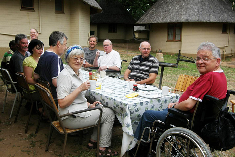 A group of guest and guest that uses a wheelchair enjoy a meal at a table at accessible height
