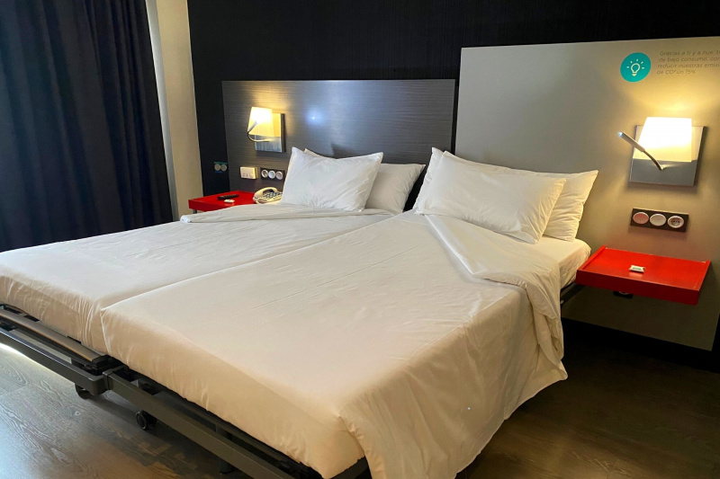 A double bed with bedside tables and lights.