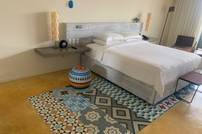 A guest room with colorful decorations and a large double bed.