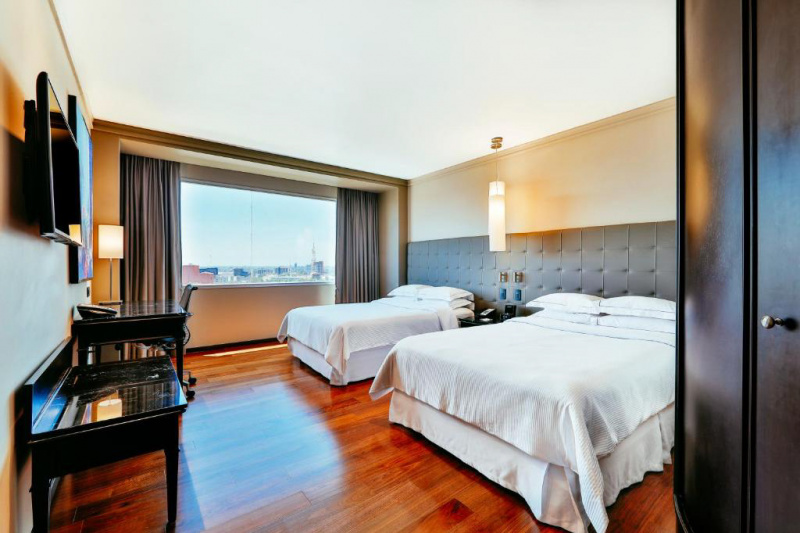 A guest room with 2 double beds, a desk and a city view.