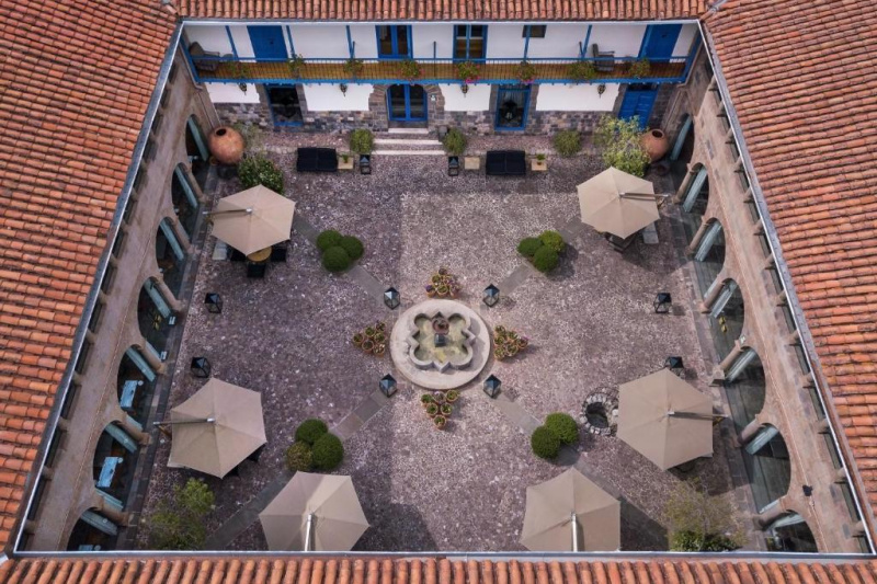 View of the inner courtyard with the fountain, seating areas and parasols.