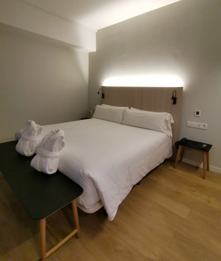 Deluxe double room with a bench and wide space on the side of the bed.