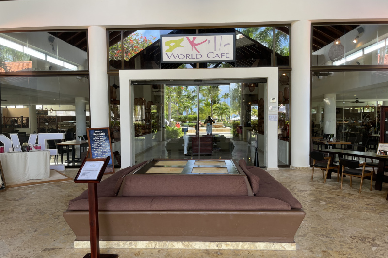 Entrance to the restaurant with seating area and large glass doors.
