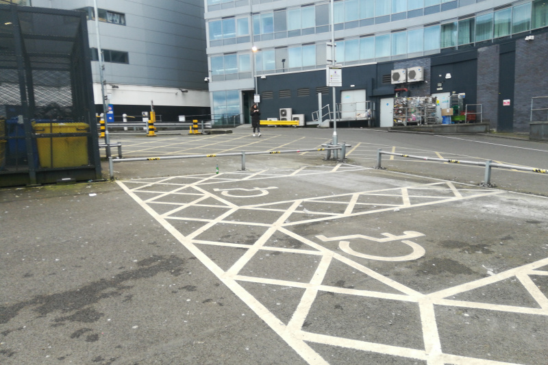 Car park in front of the hotel with accessible  parking spaces.