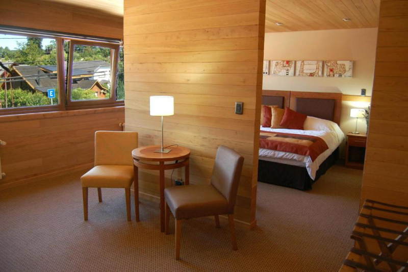 Bedroom with seating area separated by a partition.