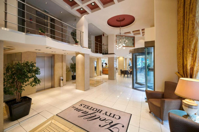 Spacious lobby with several seating areas, elevator and revolving doors.