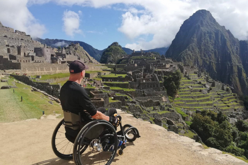 A man in a wheelchair admires the ancient Inca constructions of Machu Picchu.