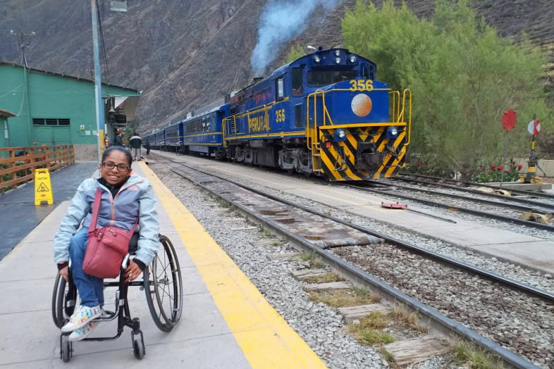A woman in a wheel chair posing in a train station