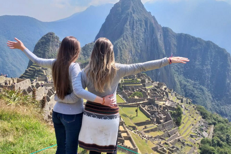 Two friends pose facing the Machu Picchu ancient constructions