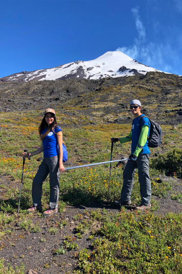 Travelers hike using hiking stick to aid hiker with low vision.