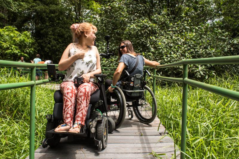 Wheel the World travelers use wheelchairs to navigate park pathways.